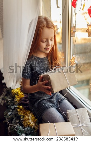 little girl with red hair in a room near the window with gifts. Christmas holidays, children's emotions. In anticipation of the holiday