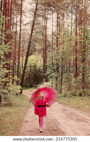 little girl with umbrella in forest - stock photo