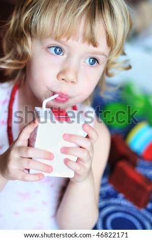 little lovely girl drinking juice from straw - stock photo