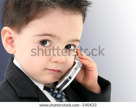 Little man discussing important business on the cell phone. Shot in studio. - stock photo