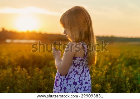 little red-haired girl holding flower in hand at sunset - stock photo