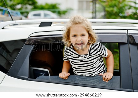 little smiling girl looking out of the car window  - stock photo