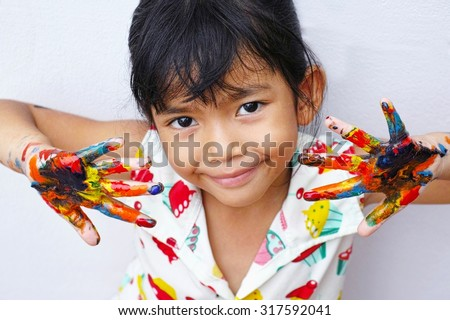 little student girl showing painted hands - stock photo