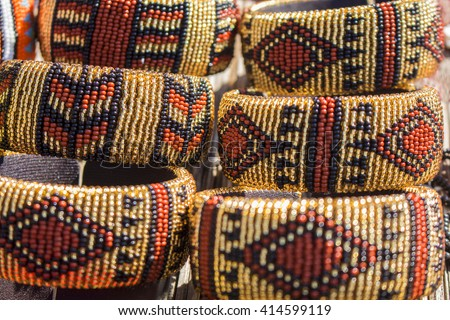 Local craft market in South Africa. Unique handmade colorful beads bracelets in beige brown tint. Craftsmanship. African fashion. Traditional accessories. - stock photo