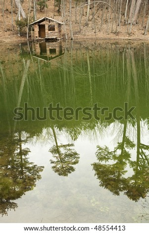 Log cabin on the shore of the lake in the forest - stock photo