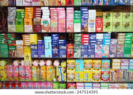 London, England - January 24, 2015: Window display of chocolate coated biscuit sticks, cookie rolls and other sweet snacks in an Asian supermarket in the Chinatown district of London, England
