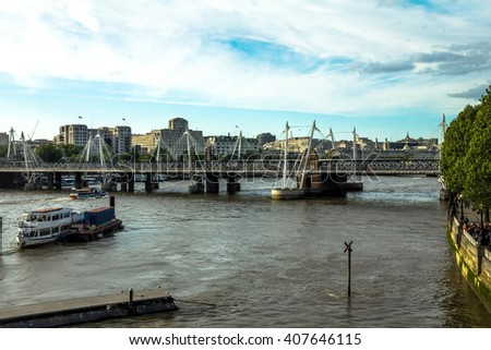 LONDON, UK - JUNE 6, 2015: Cityscape with Haugerford Bridge over  the Thames and tourist pleasure boats in late afternoon time