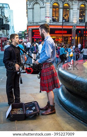 LONDON, UK - JUNE 5, 2015:  Unidentified young man talking with bagpiper in the Scottish national dress at Piccadilly Circus - stock photo