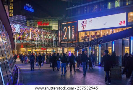 LONDON, UK - NOVEMBER 29, 2014: Stratford village square and big shopping centre decorated with Christmas lights and lots of people shopping around - stock photo