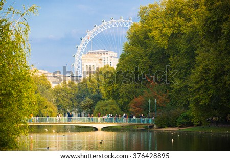 LONDON, UK - OCTOBER 4, 2016: Sant James park, lake and footbridge with distant view of London eye - stock photo