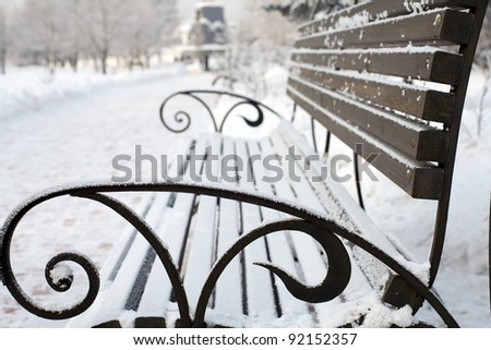 lonely bench covered with snow - stock photo
