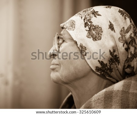 Lonely grandma in   scarf and glasses looking aside.
