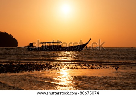 Longtail boat and sunset on Railay island, Krabi, Thailand - stock photo