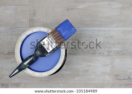 Looking down on a can of blue Paint with a loaded brush stood on a shabby style wood floor