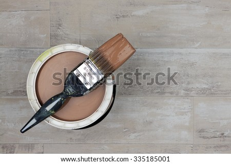 Looking down on a can of light brown Paint with a loaded brush stood on a shabby style wood floor - stock photo