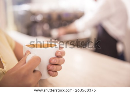 ���¡lose-up of a cup of coffee in the hands of women on the background barista. Blurred background.