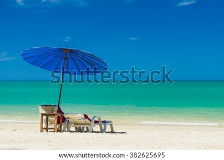 lounge chairs with sun umbrella on the tropical  beach - stock photo