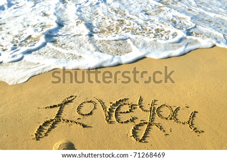 """""""Love you"""" written on a sandy beach as the ocean water approaches. - stock photo"""