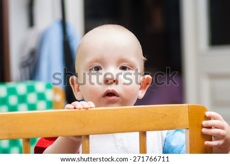 lovely baby is in a cot - stock photo