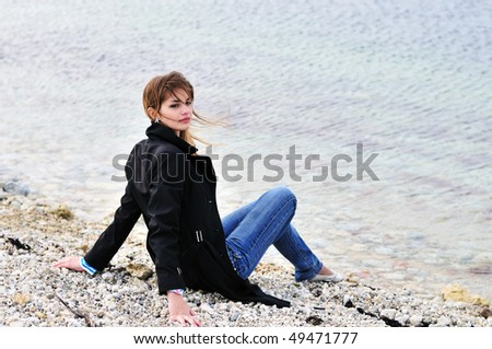 lovely teen girl sitting on the pebble close to sea in spring time