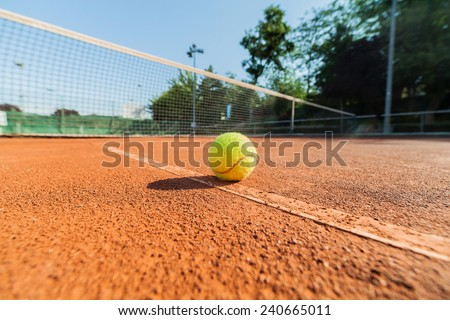 low angle closeup photograph of tennis ball on clay court - stock photo