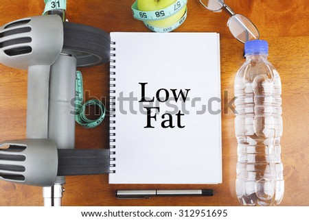 """Low Fat"" text on notebook with delicious green apple, measure tape, spectacle, a bottle of mineral water, and bodybuilding tools on wooden background - healthy, exercise and diet concept - stock photo"