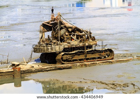 Low tide in Panama, sunken earth mover exposed in low tide on a mud flat.   - stock photo
