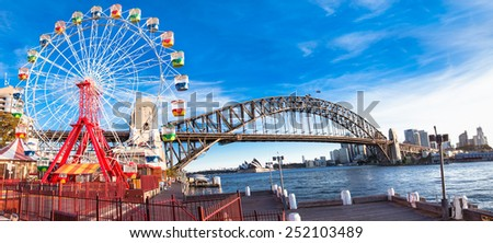 Luna park wheel with harbour bridge arch at sunset in Sydney, Australia. - stock photo