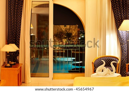 luxury interior with open balcony and swimming pool below. - stock photo