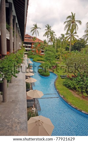 Luxury tropical hotel resort with palms and swimming pool , Bali, Indonesia.