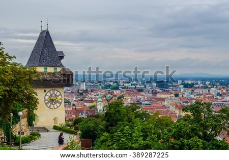 28m tall clock tower (Uhrturm) in Graz, Austria. It was built in 16th century; its handles have opposite roles - larger marks hours and smaller marks minutes. - stock photo