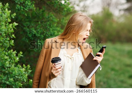 mad woman screaming on mobile phone, isolated outdoors background. Negative human face expressions, emotions, feelings, attitude - stock photo