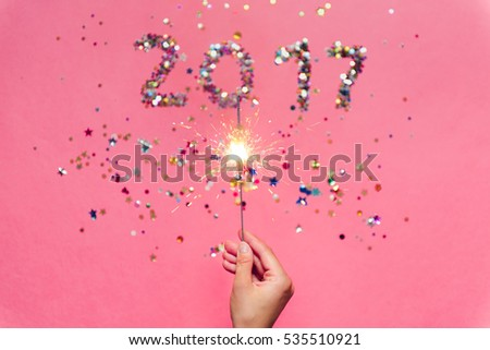 2017 made of multicolored confetti in the shape of stars and sparkler in the hand on the pink background