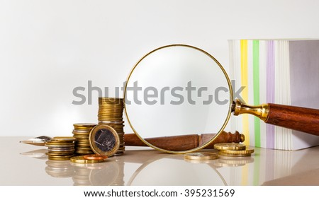 magnifying glass and coins for finance and banking concept - stock photo