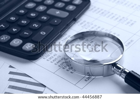 Magnifying glass with calculator on   report.blue tone