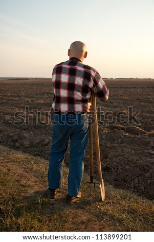 male farmer holding   shovel and pitchfork . rear view - stock photo