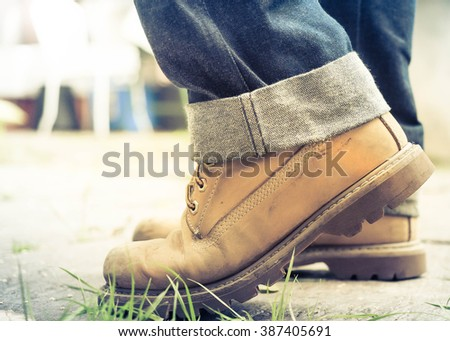 Male left foot in jeans and brown shoe stepping on street. - stock photo