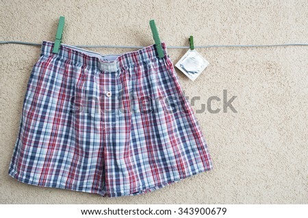 male  pants (underwear),  sealed condoms on colorful clothespins on a washing line.  space for text - stock photo