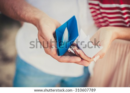 Man and woman holding paper boats, date. love, focus on hands