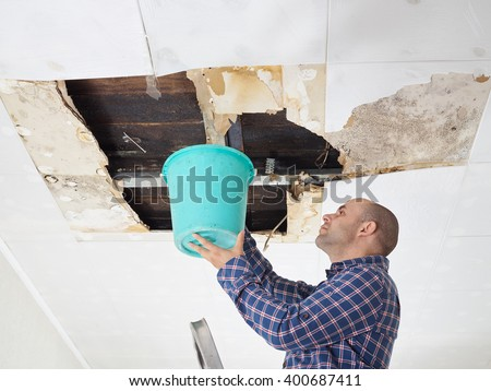 Man Collecting Water In Bucket From Ceiling. Ceiling panels damaged  huge hole in roof from rainwater leakage.Water damaged ceiling .   - stock photo