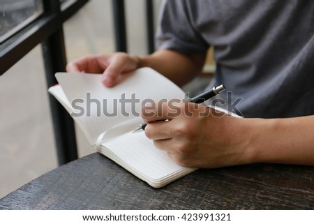 man drinking coffee and looking at the phone screen, hand writing pen on paper page on wooden table and phone.