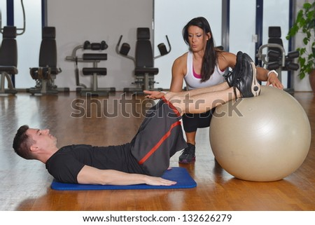 Man exercising with her personal trainer at the gym.