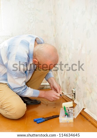 man fixing an electricity outlet within doors