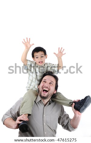 Man giving young boy piggyback ride outdoors smiling