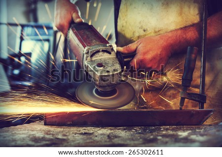 Man Grinding in workshop,shallow depth of field - stock photo