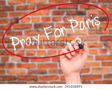 Man Hand Pray for Paris with marker on visual screen. Isolated on bricks.  - stock photo