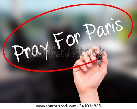 Man Hand Pray for Paris with marker on visual screen. Isolated on office.  - stock photo
