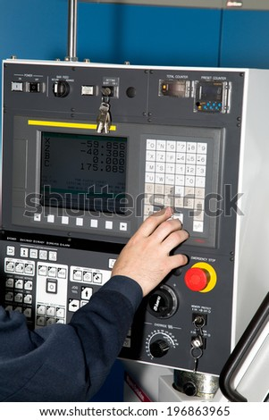 man hand  the controls of a machine CNC - stock photo