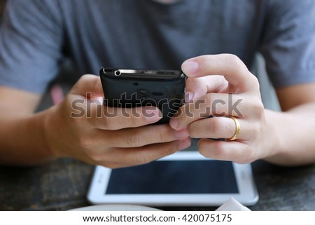 man hand use phone on wood table, internet of things , using mobile smart phone, Internet of things lifestyle with wireless communication and internet with smart phone.