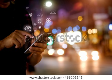 man hand using smartphone and icons hologram at street night.